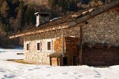 在木头的典型的高山瑞士山中的牧人小屋和石头和小犬座房子 免版税库存图片