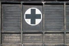 在木头的急救黑十字架在老减速火箭的救护车汽车 免版税库存照片