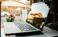 在木头的数字技术膝上型计算机在屋子里 免版税库存图片
