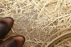 在木头的美国西方圈地牛仔靴和套索 库存照片