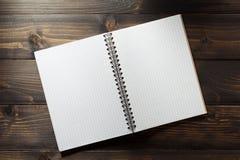 在木头的被检查的笔记本 免版税库存图片