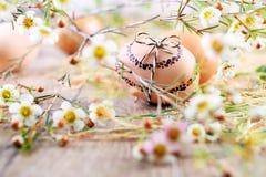 在木头的被绘的复活节彩蛋与白花和干草 免版税库存照片