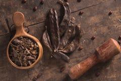 在木头的角豆树荚 免版税库存图片