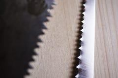 在木委员会桌关闭的两把锯 免版税库存照片
