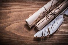 在木委员会顶视图的滚动的年迈的纸羽毛 免版税图库摄影