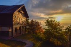 在木小屋之外的日出在山地形 免版税库存照片