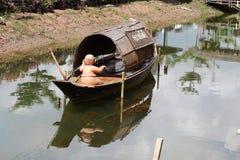 在木小船的一个被烘烤的黏土玩偶 免版税库存图片