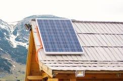 在木屋顶的太阳电池板在mountrain区域房子 图库摄影