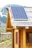 在木屋顶的太阳电池板在mountrain区域房子 库存照片