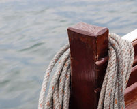 在木岗位垂悬的卷起的绳索 免版税库存图片