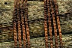在木岗位附近被包裹的生锈的金属缆绳 库存图片
