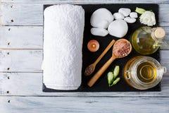 在木平台上是有一块毛巾、芳香油和石头的一个黑暗的委员会温泉治疗的 库存照片
