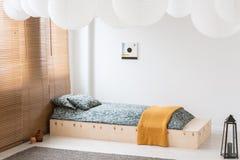 在木床上的橙色毯子在白色卧室 免版税库存照片