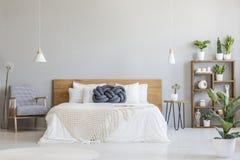 在木床上的蓝色结枕头在与p的现代卧室内部 免版税库存照片