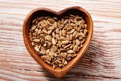 在木心脏形状碗的向日葵种子 免版税库存图片
