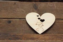 在木心脏的背景的倾心的猫 免版税库存照片