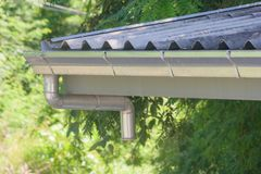 在木房子屋顶的不锈的雨天沟有阳光背景 软绵绵地集中 免版税库存照片