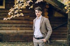 在木房子旁边的英俊的新郎立场 秋天婚礼 户外 免版税库存照片