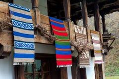 在木房子的阳台的传统保加利亚被编织的织品在Etara村庄,保加利亚 库存照片