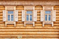 在木房子门面的Windows 老俄国乡村模式 免版税库存照片