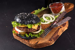 在木服务板的新鲜的自创汉堡用叉子和刀子在黑暗的背景的西红柿酱 库存图片