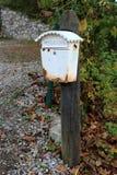在木杆的生锈的白色邮箱 免版税图库摄影
