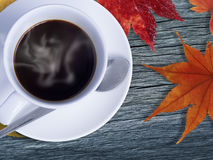 在木材和槭树的咖啡在桔子离开 免版税库存图片