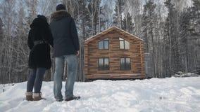 在木村庄附近的愉快的年轻夫妇身分 股票 在房子附近结合立场在森林里在冬天 影视素材