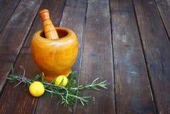 在木杵和灰浆的新鲜的迷迭香草本在木桌上 免版税库存照片