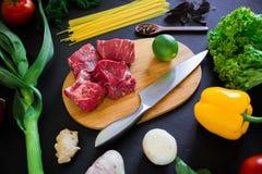 在木板、刀子、面团和新鲜蔬菜的生肉在黑暗的背景 顶视图 平的位置 背景许多饺子的食物非常肉 库存图片