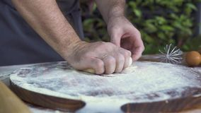 在木板和揉的面团的贝克倾吐的极少数面粉在木桌上 手做蛋糕的厨师厨师面团 股票录像