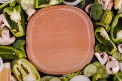 在木板和新鲜的绿色菜的一张顶视图 在倾吐的餐馆沙拉的主厨概念食物新鲜的厨房油橄榄 免版税库存照片