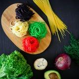 在木板材和新鲜蔬菜的多彩多姿的面团在黑暗的桌上 平的位置 顶视图 背景许多饺子的食物非常肉 免版税库存照片