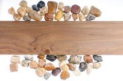 在木板材白色背景的石头 免版税库存图片
