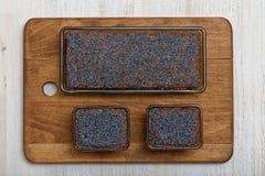 在木板材的三个柠檬鸦片蛋糕 免版税库存图片