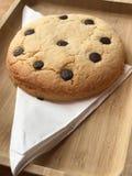 在木板材的新近地被烘烤的巧克力曲奇饼有餐巾的 免版税库存图片