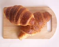 在木板材的新鲜的新月形面包早餐 库存图片