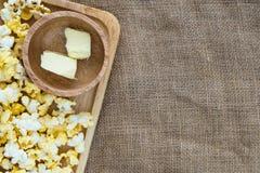 在木板材的玉米花用在木碗的黄油在黄麻袋布料 库存图片