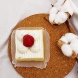 在木板材的草莓奶油蛋糕与棉花 免版税图库摄影