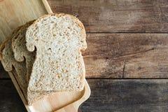 在木板材的被堆积的切片全麦三明治面包在木桌上 免版税库存照片