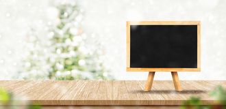 在木板条台式与抽象迷离圣诞树红色装饰球和雪秋天背景的空白的黑板菜单与bokeh 免版税库存照片