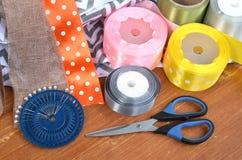 在木板条和别针设置的颜色丝带、剪刀 免版税库存照片
