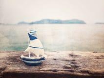 在木板条的小船玩具在与拷贝空间的海背景 免版税图库摄影