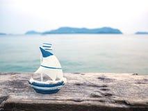 在木板条的小船玩具在海背景 库存图片
