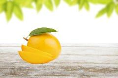 在木板条的芒果被切的和果子有叶子背景 免版税图库摄影