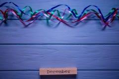 在木板条的12月消息与在蓝色木背景的多彩多姿的飘带 图库摄影