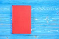在木板条背景的老红色书 空白倒空d的盖子 图库摄影