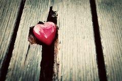 在木板条裂缝的红色心脏。爱的标志 免版税库存图片