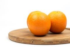 在木板的三个桔子有白色背景拷贝空间的 免版税库存图片