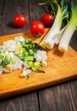 在木板的切的新鲜的韭葱用蕃茄 图库摄影